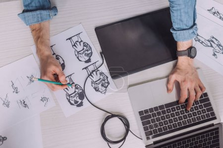 Photo for Top view of illustrator drawing cartoon sketches on paper - Royalty Free Image