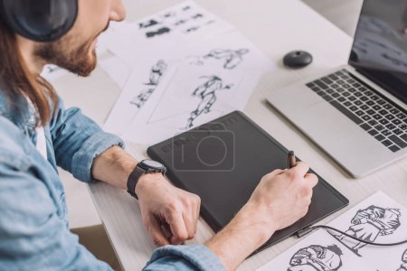 Photo for Cropped view of animator in headphones using digital tablet - Royalty Free Image
