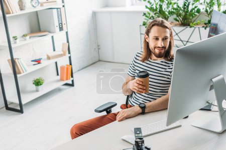 happy art editor looking at computer monitor and holding paper cup