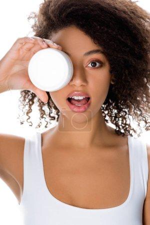 chica afroamericana sorprendida sosteniendo contenedor de plástico con crema facial, aislado en blanco