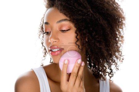 Foto de Hermosa chica afriamericana con cepillo facial limpiador de silicona, aislada en blanco. - Imagen libre de derechos
