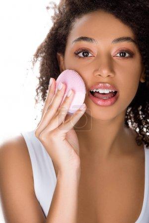 Foto de Sorprendida africa americana con brazaletes que utilizan cepillos faciales de limpieza de silicona, aislados en blanco. - Imagen libre de derechos