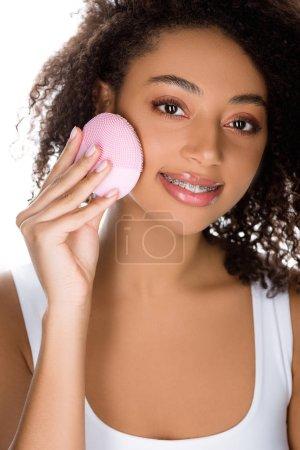 Photo pour Belle fille afro-américaine souriante avec des cas orthodontiques à l'aide d'une brosse faciale nettoyante en silicone, isolée sur blanc - image libre de droit