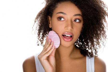 Foto de Shock african American girl using silicone cleaning facial brush, isolated on white. - Imagen libre de derechos