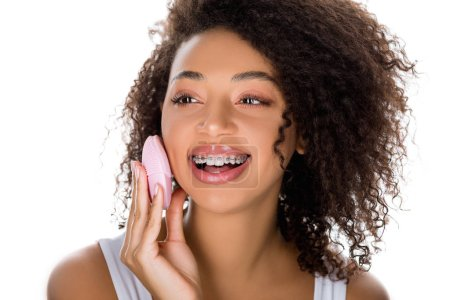 smiling african american girl with dental braces using silicone cleansing facial brush, isolated on white