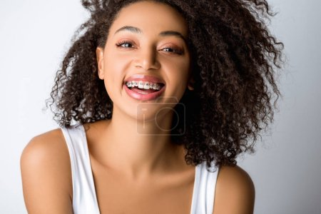 laughing african american girl with dental braces, isolated on grey