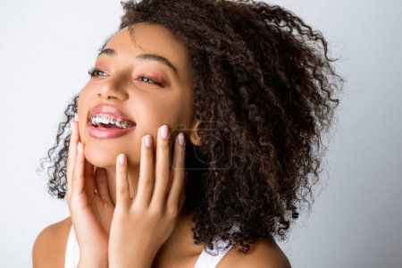 Photo for Beautiful laughing african american girl with dental braces, isolated on grey - Royalty Free Image