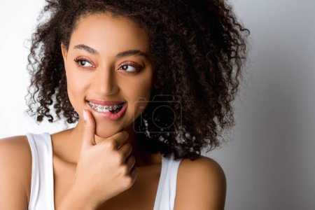 thoughtful smiling african american girl with dental braces touching lip, isolated on grey