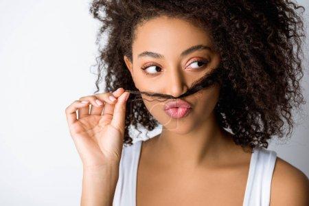 Photo pour Drôle attrayant afro-américain fille faire fausse moustache à partir de cheveux, isolé sur gris - image libre de droit