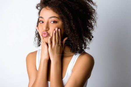 Foto de Retrato de una guapa jovencita afriamericana feliz que hace gracia graciosa, aislada en gris. - Imagen libre de derechos