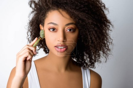 Photo for Attractive african american girl using stone facial roller, isolated on grey - Royalty Free Image