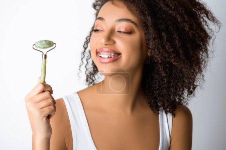 Photo pour Heureuse fille afro-américaine avec des appareils dentaires à l'aide d'un rouleau de massage naturel, isolé sur gris - image libre de droit