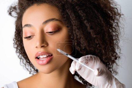 Photo pour Belle jeune femme afro-américaine faisant injection de beauté, isolé sur gris - image libre de droit