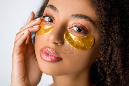 Photo for Attractive brunette african american girl with golden eye patches, isolated on grey - Royalty Free Image