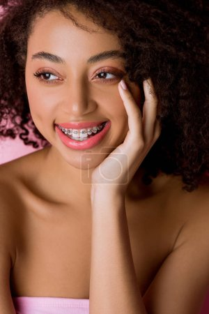 Photo for Happy attractive african american girl with dental braces, isolated on pink - Royalty Free Image