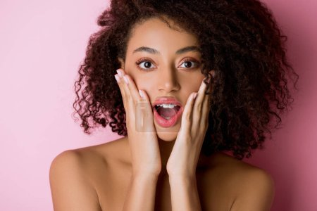 happy shocked nude african american girl with dental braces on pink