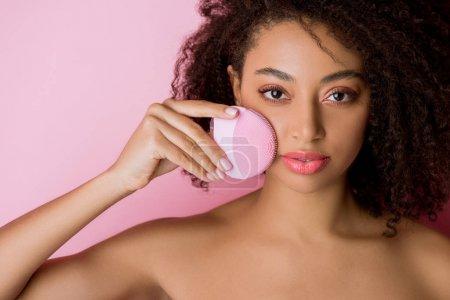 Photo pour Jolie américaine africaine nue aux yeux fermés utilisant une brosse faciale nettoyante au silicone, isolée en rose - image libre de droit