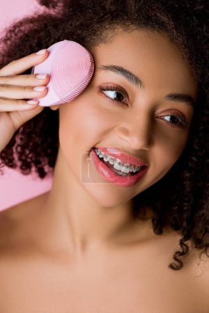 Photo pour African american woman with closed eyes using silicone cleansing facial brush, isolated on pink - image libre de droit