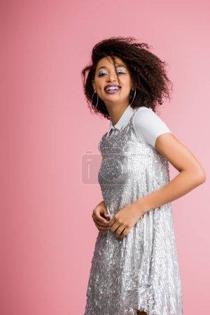 Photo pour Jolie fille afro-américaine gaie avec des appareils dentaires, avec des fards à paupières à paillettes argentées et des lèvres violettes dansant en robe paillettes, isolée sur rose - image libre de droit