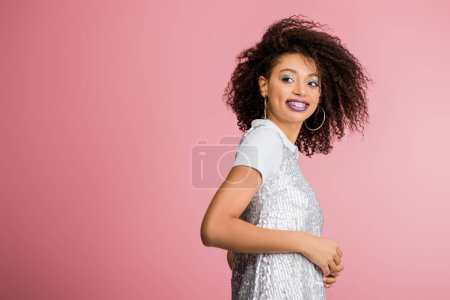 Photo pour Joyeuse fille afro-américaine avec des appareils dentaires, avec des fards à paupières à paillettes argentées et des lèvres violettes dansant en robe paillettes, isolée sur rose - image libre de droit
