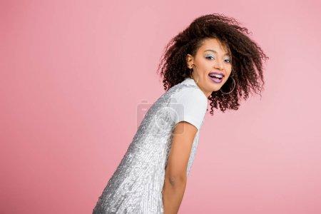 Photo pour Souriante afro-américaine aux bretelles dentaires, aux fards à paupières argentés à paillettes et aux lèvres violettes dansant en robe paillettes, isolée sur rose - image libre de droit