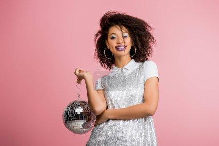 Photo pour Heureux émotionnel afro-américain fille en paillettes robe tenant boule disco, isolé sur rose - image libre de droit