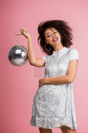 Photo for Cheerful african american girl in paillettes dress holding disco ball, isolated on pink - Royalty Free Image
