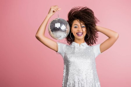 Photo for Smiling african american girl in paillettes dress holding disco ball, isolated on pink - Royalty Free Image