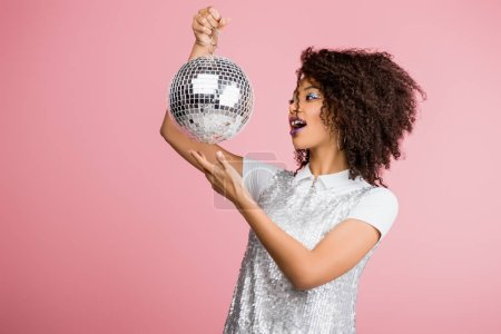 Photo pour Excité afro-américaine fille en maillettes robe tenant boule disco, isolé sur rose - image libre de droit