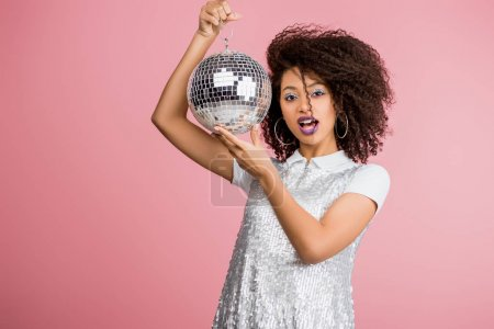 Photo for Shocked african american girl in paillettes dress holding disco ball, isolated on pink - Royalty Free Image
