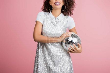 Photo pour Heureux afro-américaine fille en paillettes robe tenant boule disco, isolé sur rose - image libre de droit