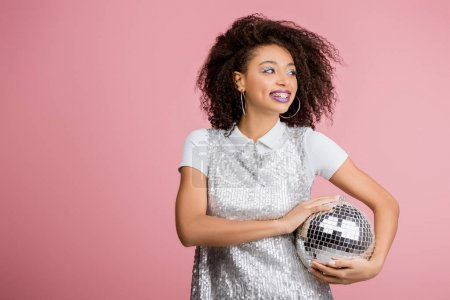 Photo for Pretty smiling african american girl in paillettes dress holding disco ball, isolated on pink - Royalty Free Image