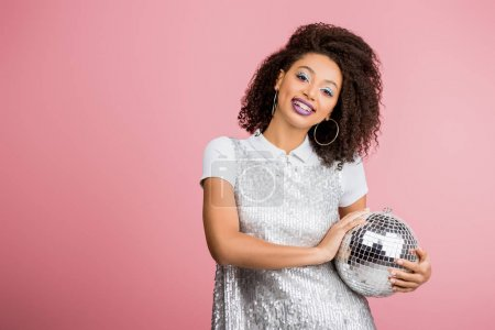 Photo for Beautiful smiling african american girl in paillettes dress holding disco ball, isolated on pink - Royalty Free Image