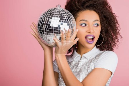 Photo for Excited african american girl in paillettes dress holding disco ball, isolated on pink - Royalty Free Image