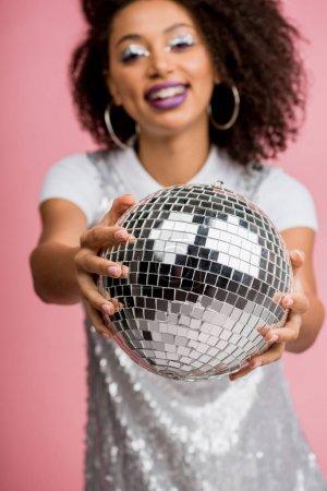 Photo pour Foyer sélectif de fille afro-américaine heureuse en robe paillettes tenant boule disco, isolé sur rose - image libre de droit