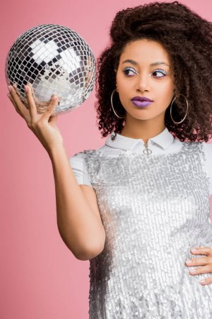 Photo for Beautiful african american girl in paillettes dress holding disco ball, isolated on pink - Royalty Free Image