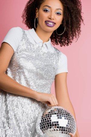 Photo pour Heureuse jeune femme afro-américaine en robe de paillettes tenant le ballon disco, isolée sur rose - image libre de droit