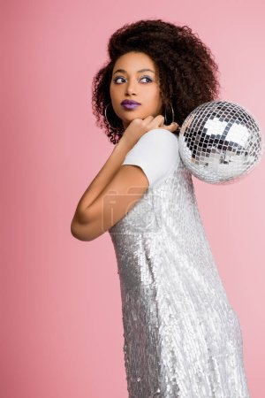 Photo for Stylish african american girl in paillettes dress holding disco ball, isolated on pink - Royalty Free Image