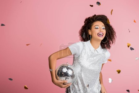 smiling african american girl in paillettes dress holding disco ball, isolated on pink with confetti