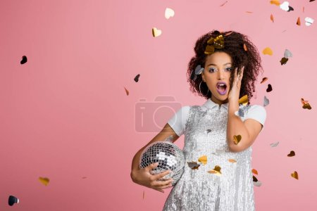 Photo for Shocked african american girl in paillettes dress holding disco ball, isolated on pink with confetti - Royalty Free Image