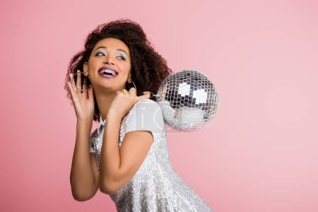 Photo for Smiling african american girl in paillettes dress holding disco ball, isolated on pink with confetti - Royalty Free Image