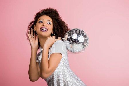 Photo pour Souriant afro-américaine en robe de paillettes tenant boule disco, isolé sur rose avec confettis - image libre de droit