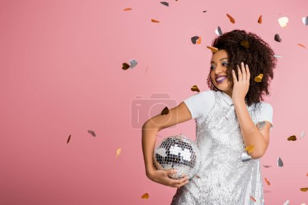 attractive cheerful african american girl in paillettes dress holding disco ball, isolated on pink with confetti