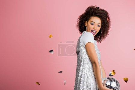 Photo pour Gai afro-américaine fille en maillettes robe tenant boule disco, isolé sur rose avec confettis - image libre de droit