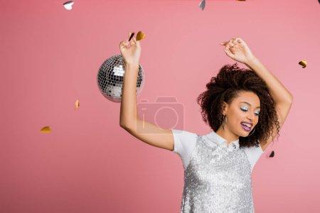 Photo pour Heureux attrayant afro-américain fille en maillettes robe danse avec boule disco, isolé sur rose avec confettis - image libre de droit
