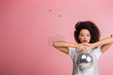 Photo pour Attrayant afro-américain fille en maillettes robe tenant boule disco, isolé sur rose avec confettis - image libre de droit