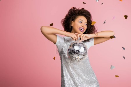 happy african american girl in paillettes dress holding disco ball, isolated on pink with confetti