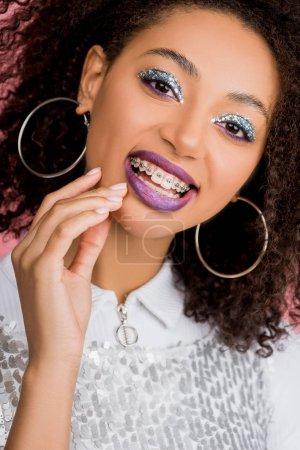 Photo pour Heureuse fille afro-américaine avec des bretelles dentaires, avec des fards à paupières à paillettes argentées et des lèvres violettes portant une robe paillettes, isolée sur rose - image libre de droit
