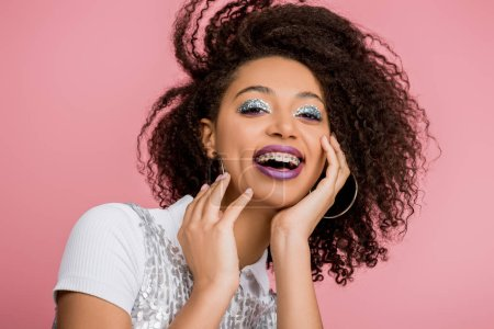 excited african american girl with dental braces, with silver glitter eyeshadows and purple lips wearing paillettes dress, isolated on pink