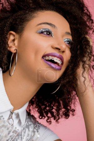 Foto de Jovencita afriamericana alegre con cordones dentales, con ojivas brillantes plateadas y labios púrpuros vestidos con paillettos, aislada en rosa. - Imagen libre de derechos